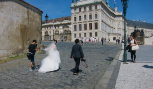 An Asian couple and their photographer make their way to Prague castle. Prague, to many Easterners, is viewed as a very romantic, historic town.